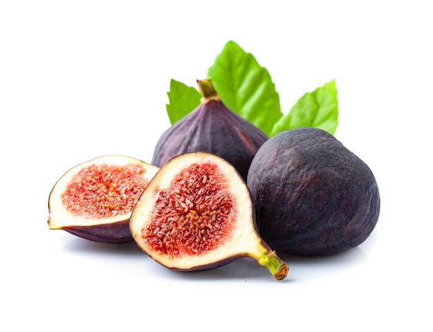 Сладкие плоды инжира с листьями на белом фоне