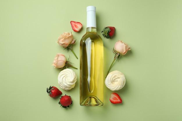 달콤한 음식과 녹색 배경에 빈 와인 병