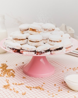 Sweet food dusted with powder sugar on cake stand with wheat grain and milk bowl over checkered fabric