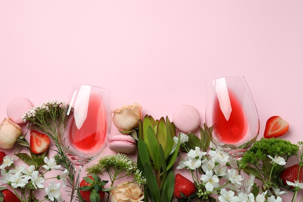 Sweet food, flowers and wine on pink background