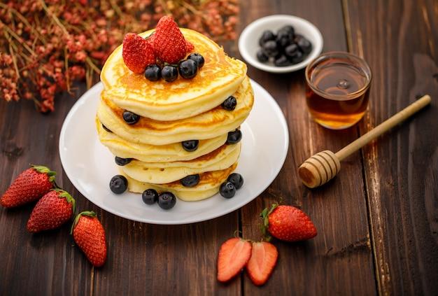 甘い食べ物。ぼやけた木製の背景に白いプレートにブルーベリー、イチゴ、蜂蜜とおいしいパンケーキのスタック。