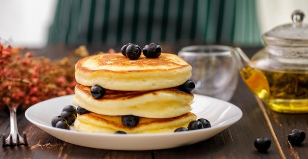 甘い食べ物。フォークでおいしいパンケーキのスタックは、ブルーベリーと蜂蜜、ぼやけた木製の背景に白いプレートのティーポットを置きます。