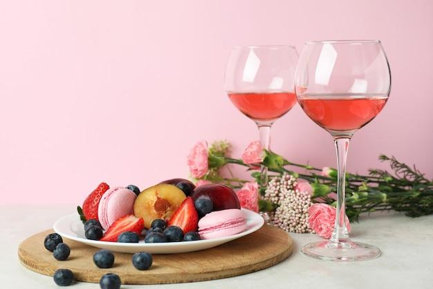 Сладкая еда, вино и цветы на розовом фоне