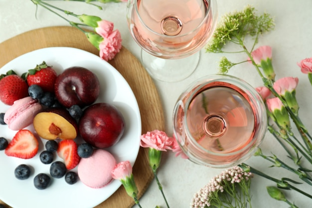 Sweet food, wine and flowers on white textured background