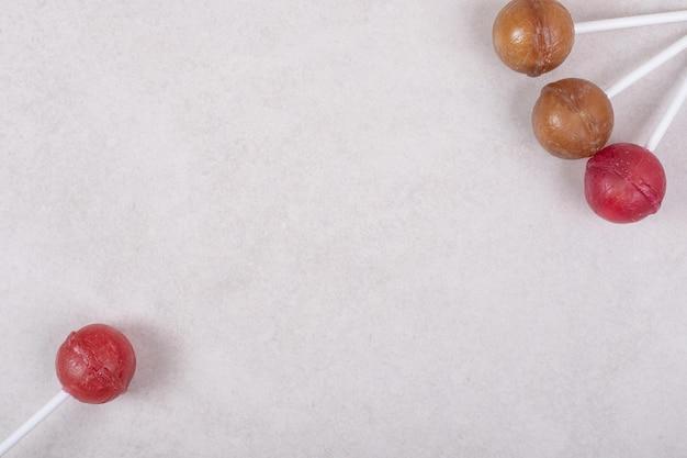 Dolci quattro lecca-lecca su uno spazio bianco.