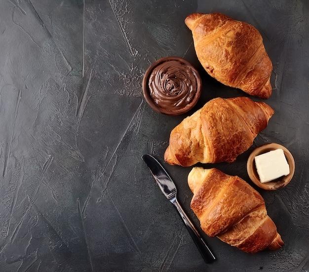 Сладкий французский круассан с шоколадным кремом и маслом на черных бетонных столах.