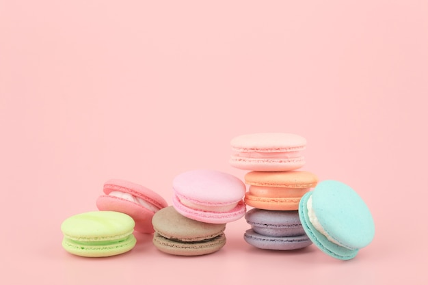 Sweet french macaroons cake with vintage pastel colored tone on pink background.