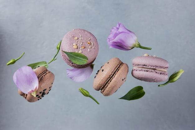 달콤한 프랑스 마카롱은 회색 표면에 꽃과 섞여 떨어집니다. 파스텔 컬러 비행 마카롱 쿠키. 음식, 요리 및 요리 개념