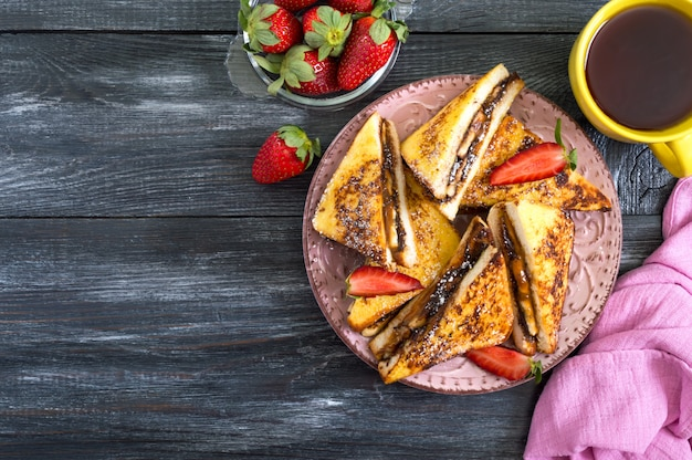 Sweet french toasts with banana, chocolate, strawberries on a wooden surface. tasty breakfast. top view