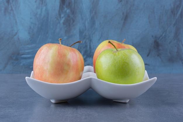 Сладкие свежие яблоки в тарелке, на темной поверхности