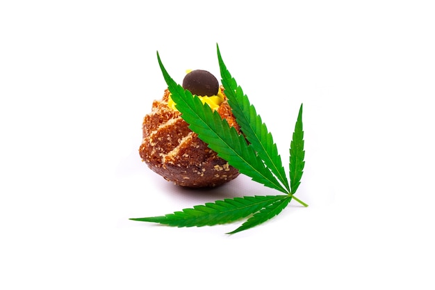 Sweet fresh cupcake with green leaf of marijuana plant isolated on white background, cannabis butter sweets.