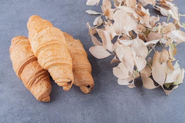 Croissant francese fresco dolce su sfondo grigio.