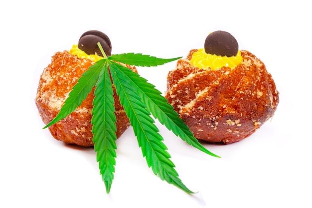 大麻油と甘い新鮮なマフィン、白い壁に分離されたマリファナとお菓子。