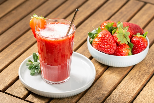 Sweet fresh strawberry juice on wooden table. healthy food