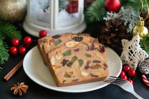 Куски торта сладостных плодоовощ на белой плите положили на таблицу черного гранита в взгляде со стороны с украшением рождества.