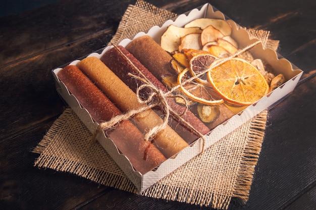Сладкие фруктовые закуски в подарочной упаковке - пастилки и сухофрукты.