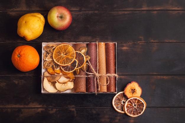 Сладкие фруктовые закуски в упаковке - пастилки и сухофрукты.