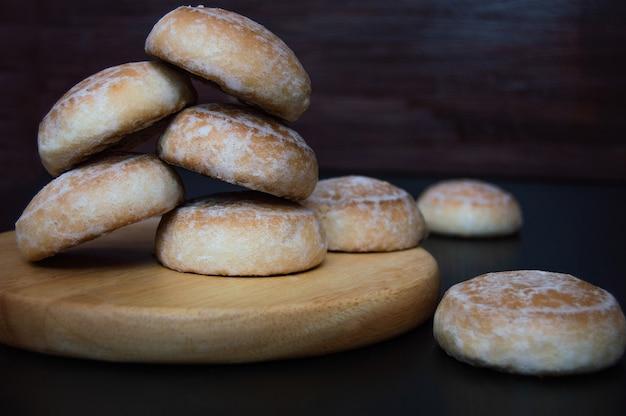 Сладкие пряники с белой сахарной глазурью, вид сверху на деревянной подставке