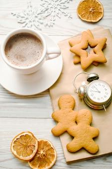 甘いジンジャーブレッドスター、カップマグコーヒーラテ付きの男の形のクッキー、お祝いのクリスマスフードデザートの装飾。クリスマス、お正月飾り、目覚まし時計。冬の休日のコンセプト。