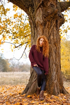 Sweet girl in the autumn forest, loneliness and melancholy