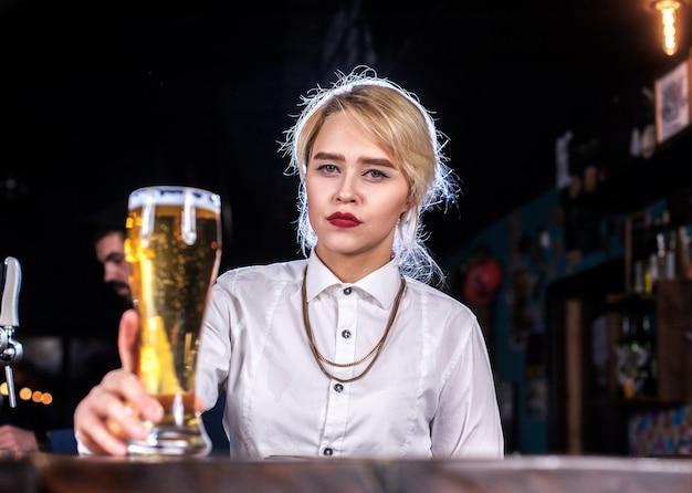 술집에서 안경에 신선한 알코올 음료를 붓는 바텐더 달콤한 소녀