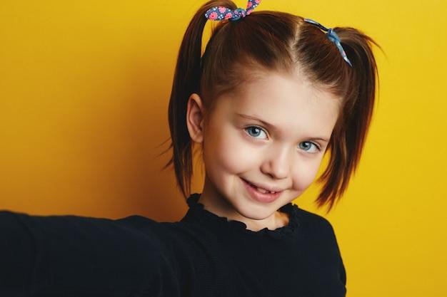 Милая девушка весело улыбается, принимая селфи на желтом фоне