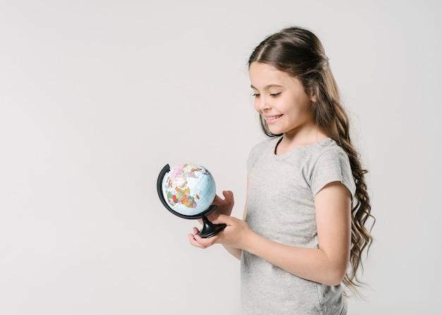 Сладкая девочка держит глобус в студии