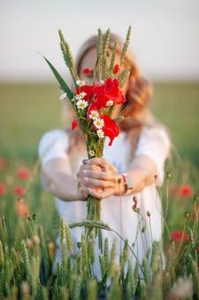 赤いケシの花を手で保持している甘い女の子。写真をクローズアップ。