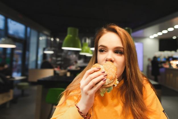 甘い女の子は両手で大きなおいしいハンバーガーを保持しています。