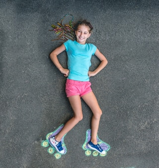 Милая девушка в роликовых коньках нарисована мелом