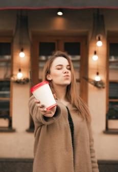 甘い女の子は彼女の手でキスと紙コップのコーヒーを示し、ベージュのコートを着て、レストランの壁の背景に立っています