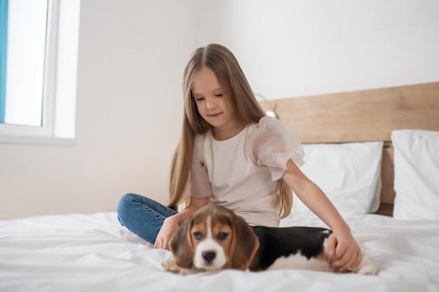 Милая девочка сидит на кровати и играет со своим щенком
