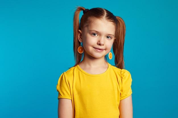 Милая девушка в желтой футболке и оранжевых серьгах улыбается во время позирования