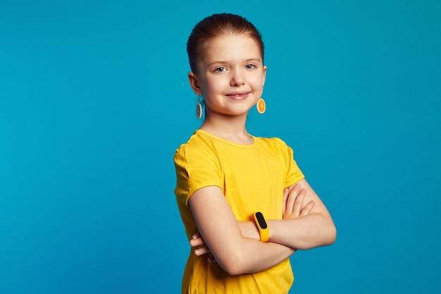 Sweet girl wearing yellow tshirt and orange earrings smiling while posing