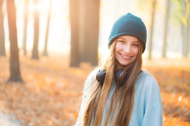 秋の公園でヘッドフォンで甘い女の子