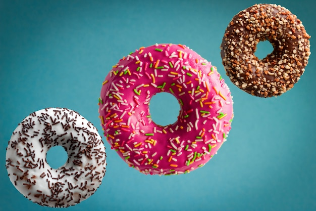 Sweet  glazed donuts flying over blue background, junk food concept