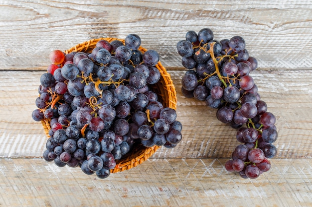 Sweet grapes in a wicker basket on a wooden background. flat lay.