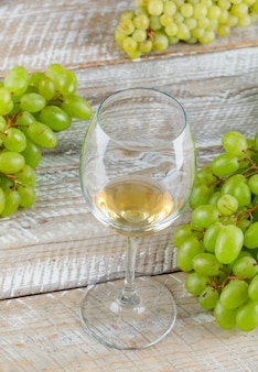 Sweet grapes with drink close-up on a wooden background