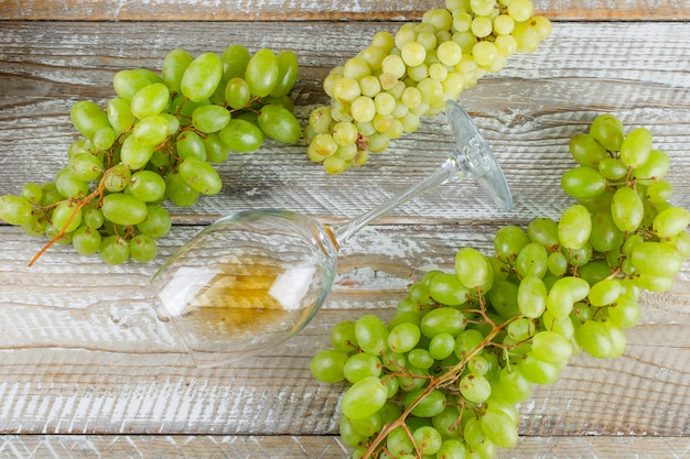 Sweet grapes with drink flat lay on a wooden background