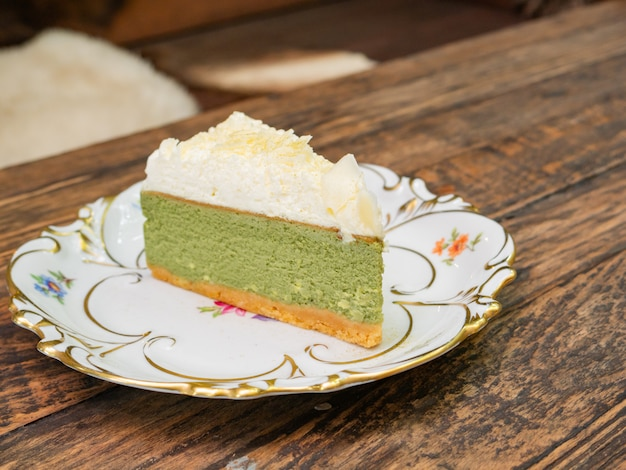 Sweet green tea cheesecake topping with white chocolate put on a white plate that placed on solid wood table.