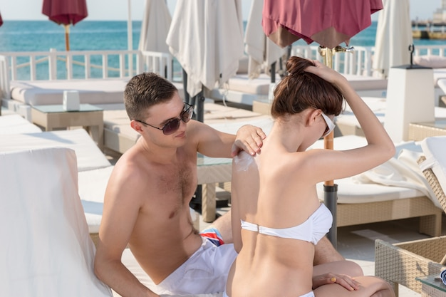 Sweet handsome young boyfriend applying sunscreen lotion on his girlfriend while sitting on lounge chair at the resort.