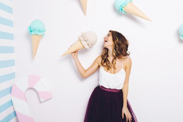 巨大なコーンアイスクリームを楽しんでチュールスカートで魅力的なファッショナブルな若い女性の甘い幸せな瞬間。夢見て、美味しくて、楽しんで、幸福、笑顔。