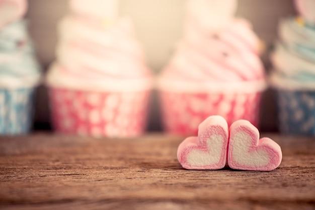 ヴィンテージ色の木製テーブル上のマシュマロの甘い心臓の形