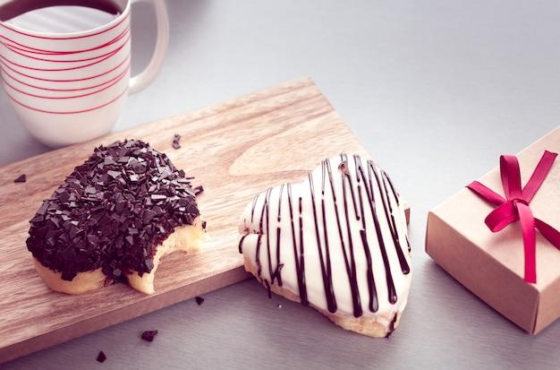 Пончики в форме сердца с кофе Premium Фотографии