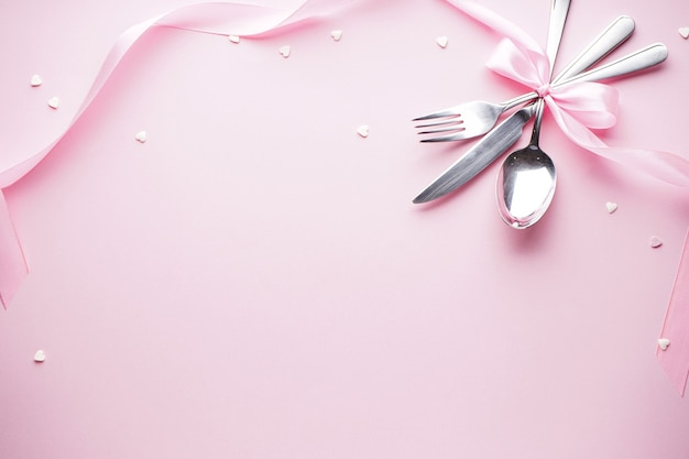 Сладкие сердца и столовые приборы на белой тарелке с розовой лентой на розовом фоне, плоская планировка. день святого валентина. день матери фон. концепция любви.