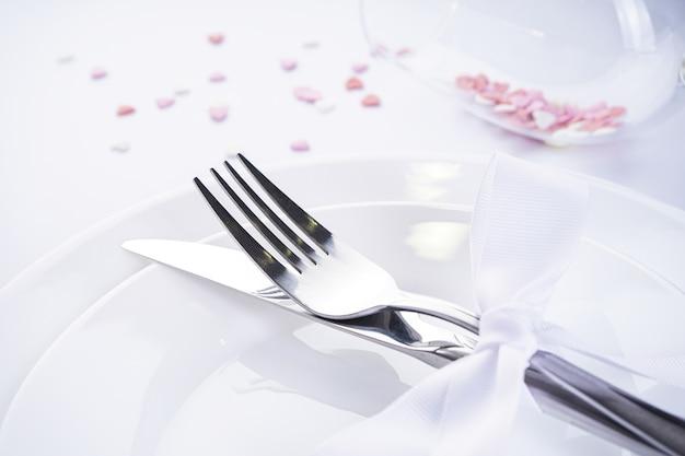 Сладкие сердечки в стакане со столовыми приборами и белой лентой на белом фоне. день святого валентина. концепция любви. с местом для текста.