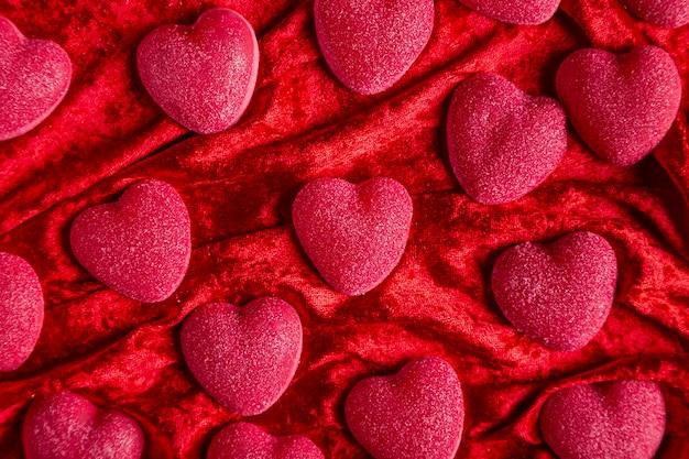 Сладкие сердечки на красной бархатной ткани