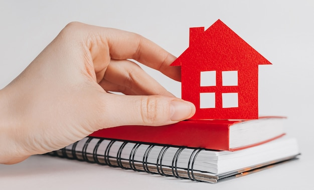 Sweet home. estimating and paying house tax. woman holding red house with her hands and notepad in copy space white background