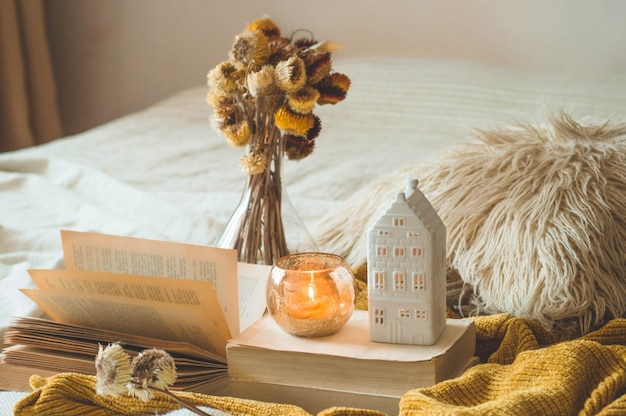 Sweet home. still life details in home interior of living room. dried flower vase and candle,  autumn decor on the books. read, rest. cozy autumn or winter concept.