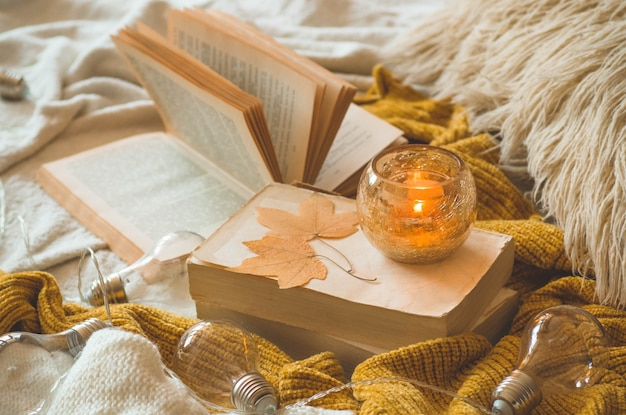 Sweet home. still life details in home interior of living room. sweaters and candle,  autumn decor on the books. read, rest. cozy autumn or winter concept.